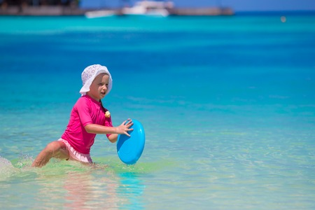 children swimsuit: Little girl playing  on a tropical white beach
