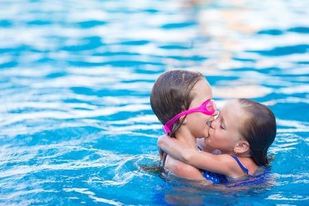 maillot de bain fille: Petites filles adorables jouant dans la piscine extérieure