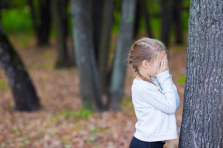 seek: Little girl playing hide and seek in autumn forest outdoors