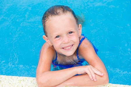blue eyes girl: Closeup little girl having fun in outdoor swimming pool Stock Photo