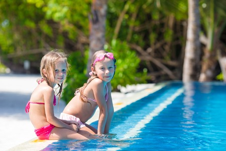 beach girl: Adorable little girls playing in outdoor swimming pool Stock Photo