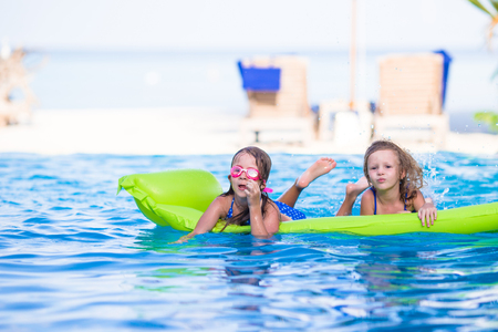 little girl swimsuit: Adorable little girls playing in outdoor swimming pool Stock Photo