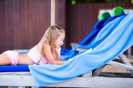 sunbathe: Adorable little girl on beach lounger outdoors