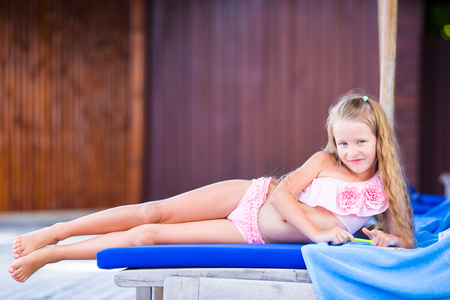 laying: Adorable little girl on beach lounger outdoors