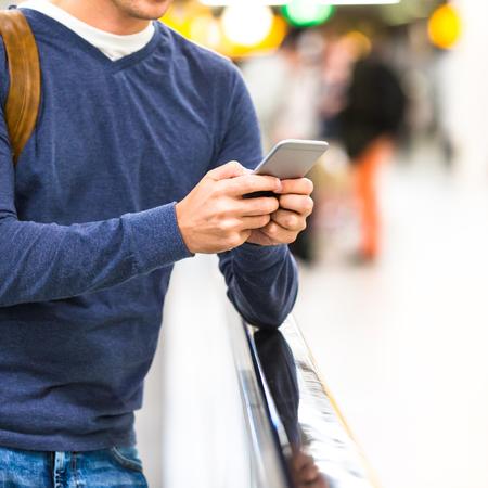 gente aeropuerto: Hombre con el morral que sostiene el teléfono celular y el embarque de pasaportes en aeropuerto esperando el vuelo