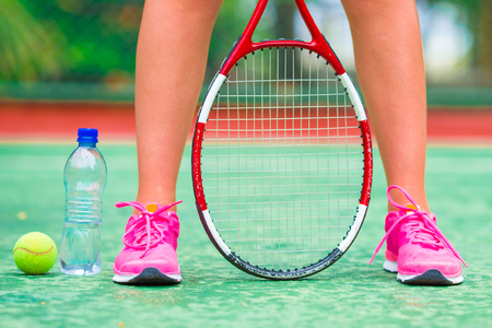 racquet: Close up of sneakers near the tennis racquet and ball Stock Photo