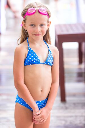 children swimsuit: little girl enjoy vacation in the swimming pool