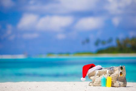 Blue bag, straw hat, flip flops and towel on white beach Standard-Bild