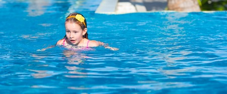 children swimsuit: Happy beautiful girl having fun in outdoor swimming pool