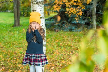 hide and seek: Little girl playing hide and seek in autumn forest outdoors