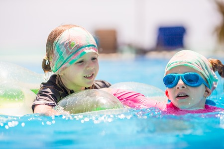 girl glasses: Adorable little girls playing in outdoor swimming pool Stock Photo