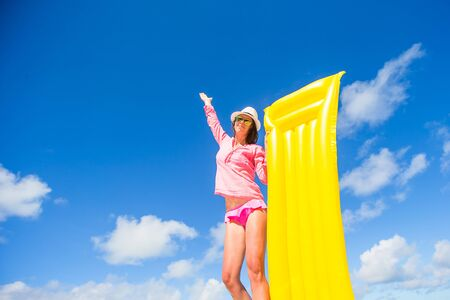 suncare: Young happy woman relaxing wit yellow beach