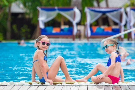 kids playing beach: Adorable little girls playing in outdoor swimming pool Stock Photo