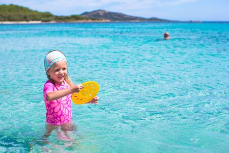 little girl swimsuit: Little girl playing flying disk on a tropical white beach Stock Photo