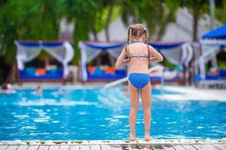 Happy beautiful girl having fun in outdoor swimming pool