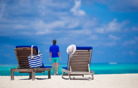 blue romance: Lounge chairs with stripe bag and hat on tropical beach at Maldives Stock Photo