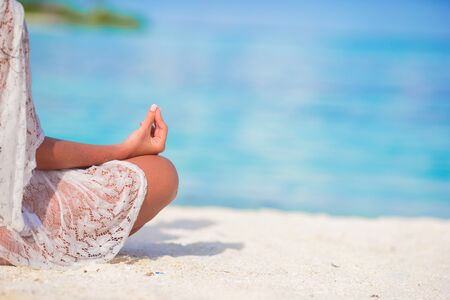 poses: Happy relaxed young woman practicing yoga outdoors at the beach