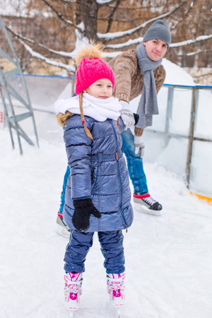 skating rink: Young father and adorable little girl on a skating rink