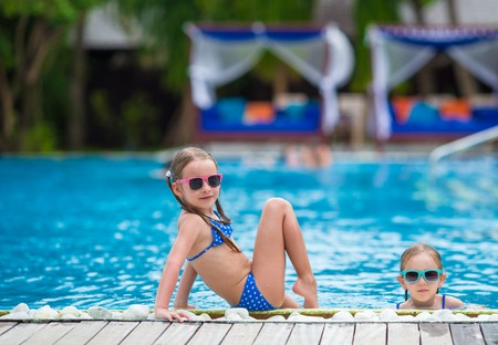 to black: Adorable little girls playing in outdoor swimming pool Stock Photo