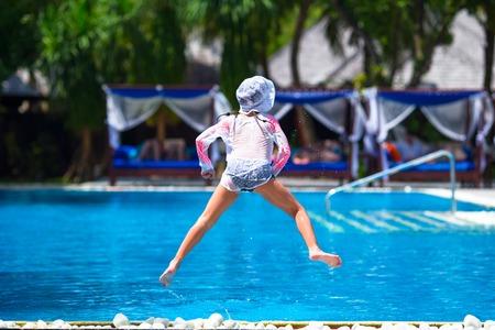 young black girl: Happy beautiful girl having fun in outdoor swimming pool