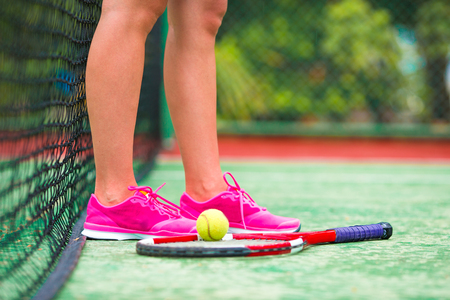 racquet: Closeup of shoes with the tennis racquet and ball outdoors