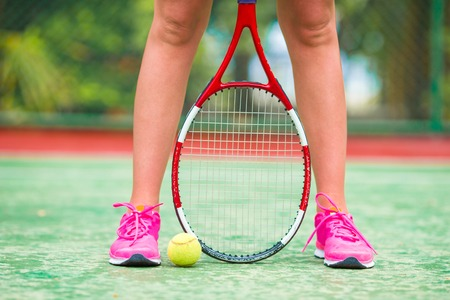 tennis racquet: Closeup of shoes with the tennis racquet and ball outdoors