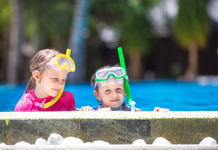 little girl beach: Adorable little girls playing in outdoor swimming pool Stock Photo
