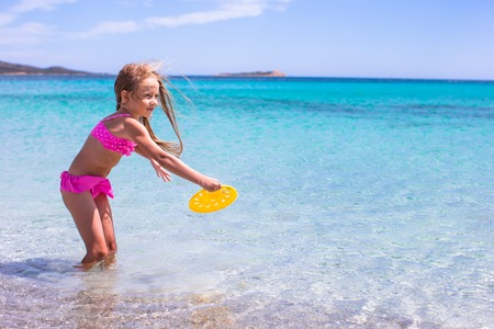 children swimsuit: Little girl playing frisbee on a tropical white beach