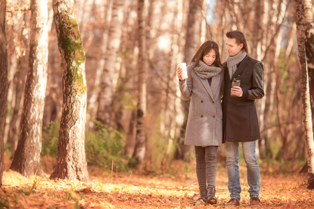 twosome: Happy family of two walking in autumn park on a sunny fall day