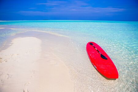 island: surfboard on white sandy beach with turquoise water