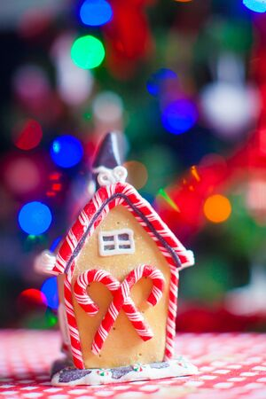 casita de dulces: Gingerbread fairy house on a background of bright Christmas tree with light garland Foto de archivo
