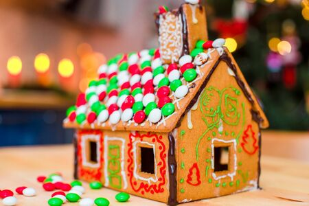 pain: Gingerbread fairy house on a background of bright Christmas tree with light garland Banque d'images