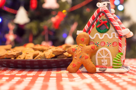 galleta de jengibre: Cute gingerbread man in front of his candy ginger house background the Christmas tree lights Foto de archivo