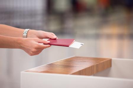 passeport: Gros plan des mains de femmes titulaires d'un passeport et de carte d'embarquement à l'aéroport
