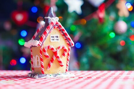 gingerbread cookie: Gingerbread fairy house on a background of bright Christmas tree with light garland Stock Photo