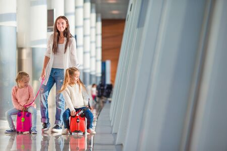 air baby: Mom and little daughter with luggage and boarding pass at airport terminal