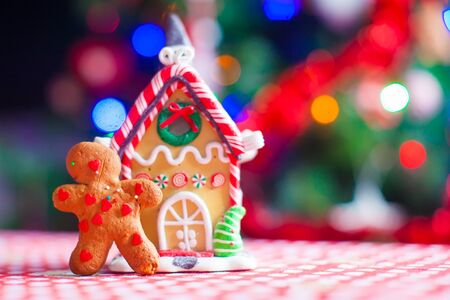 gingerbread cookie: Cute gingerbread man in front of his candy ginger house background the Christmas tree lights Stock Photo