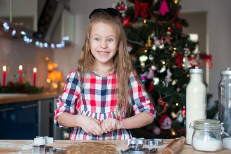 baking christmas cookies: Happy adorable girl baking Christmas cookies at home