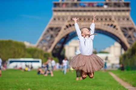 Eiffel Tower: Adorable little girl in Paris background the Eiffel tower in France
