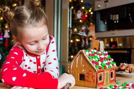 home decorating: Little adorable girl decorating gingerbread house for Christmas at home
