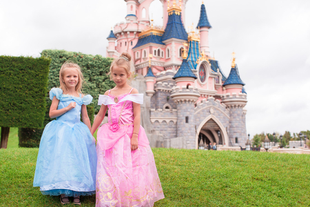 cinderella dress: Little happy girls in fairy-tale park Disneyland Editorial