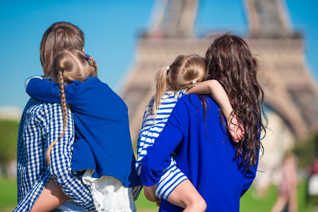 urban parenting: Happy family of four having fun together in Paris near the Eiffel tower