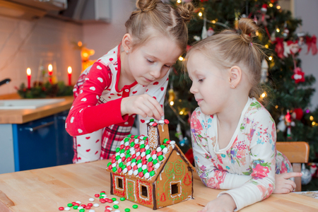 home decorating: Little adorable girls decorating gingerbread house for Christmas at home