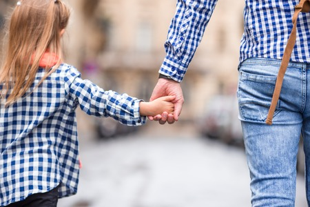 Hands of man and girl holding together on street at european city
