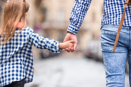 niños caminando: Manos del hombre y de la muchacha que se ligan en la calle en la ciudad europea