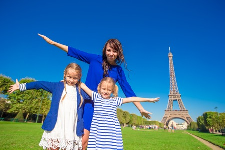 urban parenting: Happy family of three having fun together in Paris near the Eiffel tower Stock Photo