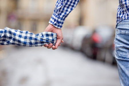 adult hand: Hands of man and girl holding together on street at european city