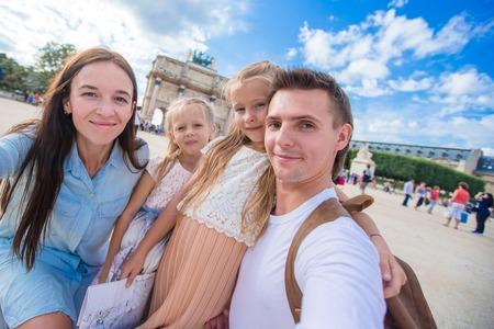 urban parenting: Happy family of four having fun together in Paris