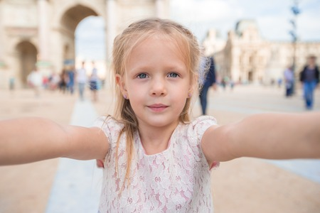 cute little girl smiling: Adorable little girl taking selfie with mobile phone outdoors in Paris, France
