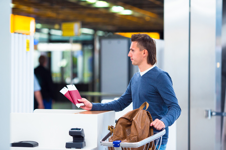 flying man: Closeup of male hands holding passports and boarding pass at airport